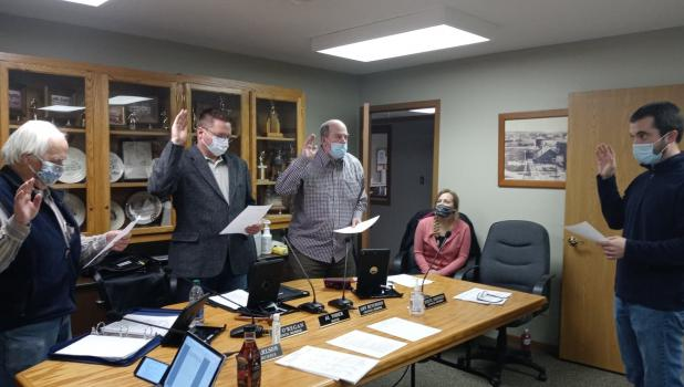 Motley Clerk/Treasurer Curt Bryniarski facilitated a swearing-in ceremony for newly elected city officers this past Nov. 3, 2020. Pictured taking the oath of office are, from left, council member Pat O'Regan, Mayor Al Yoder; and council member Steve Johnson. In the background is council member Amy Hutchison.  (Staples World photo by Dawn Timbs)