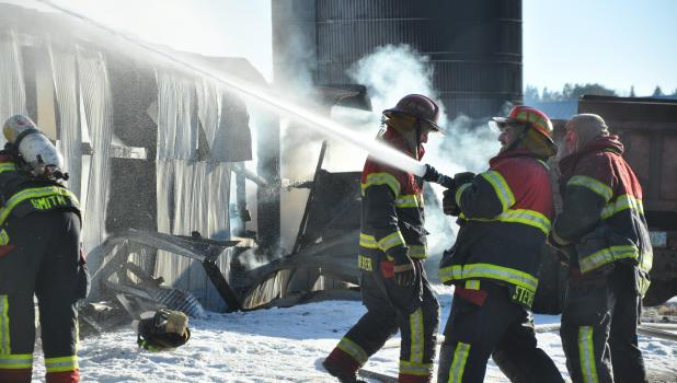On a below zero day smoke and steam rose into the morning sky while Motley firefighters fought the fire from the south side of the barn as the rafters and metal siding started bowing out from the heat. See more photos on page 2a. (Staples World photo by Janice Winter)