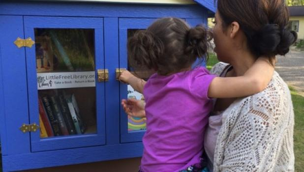 Maria Wolfe and her daughter Natalie of Brainerd  stopped by the Little Free Library in rural Motley recently.  It is located in Scandia Valley Township, near Maria Wolfe's parents' home (Bob and Carolyn Lohman) on West Shamineau Dr. (Submitted photo)