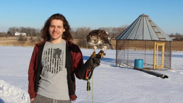 Colton Rau with his red-tailed hawk, in the background is the outdoor pen where Rau allows his hawk to get exercise when they are not out hunting. He also built an enclosed mew (raptor house) where the hawk can stay warm and dry during the winter. (Staples World photo by Mark Anderson)