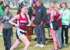 Kiera Dumpprope carries the baton in the winning 4x800 meter relay, as her teammates and Coach Bruce Fuhrman check the split of her first lap. (Staples World photo by Mark Anderson)